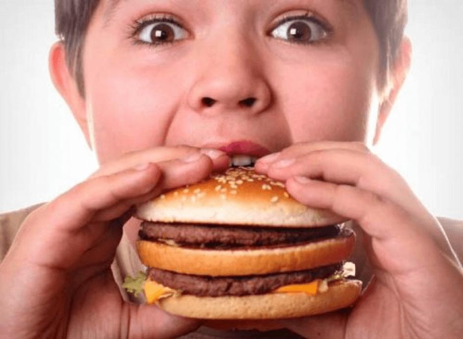 Jongen die hamburger eet