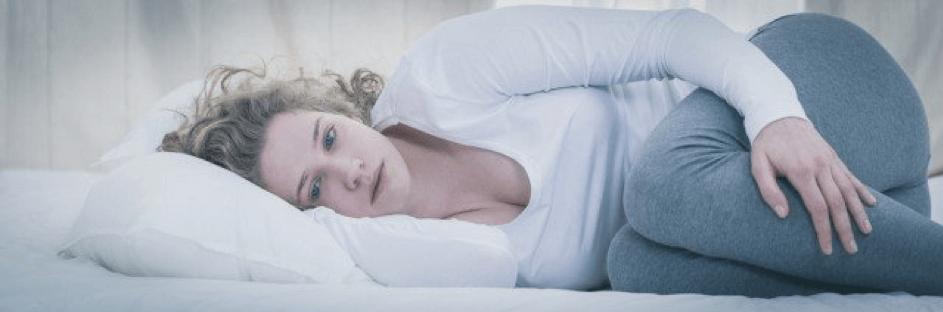 Vrouw liggend met opgetrokken knieën.