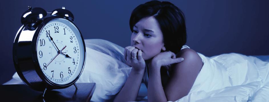 Vrouw ligt wakker met insomnia naast wekker